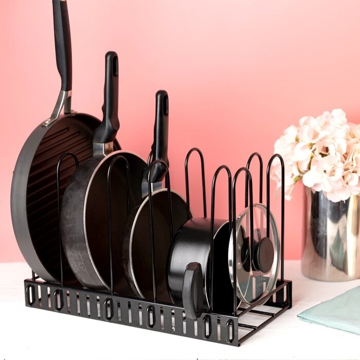 The black pan organizer holding pots and pans of varying sizes