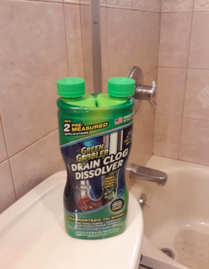 Reviewer places green container of Green Gobbler Drain Clog Dissolver on white bathroom countertop after using it on a tub