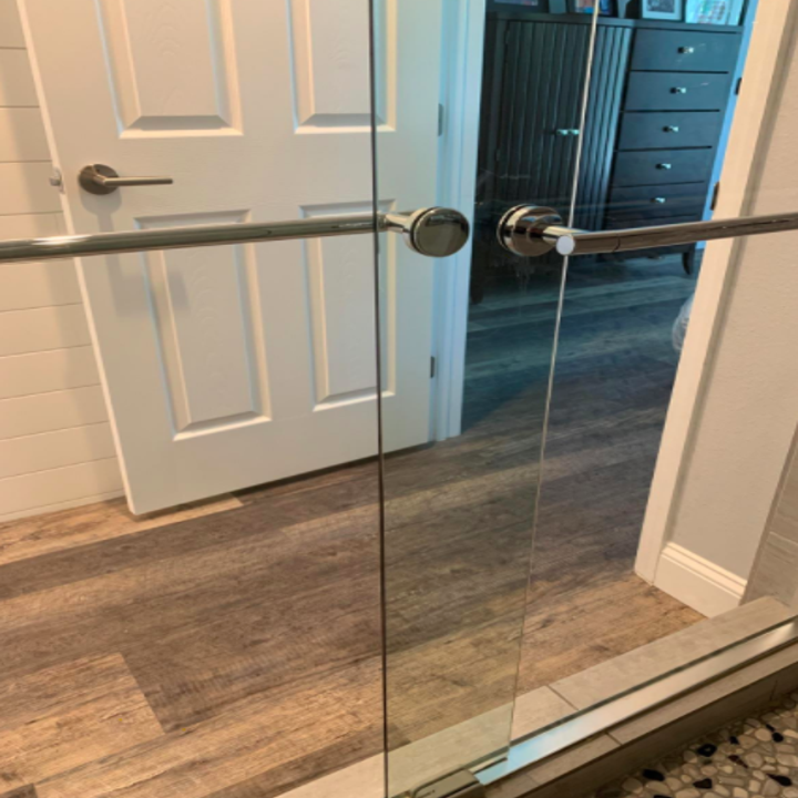 Reviewer's sparkling clean shower door after using the hard water stain remover