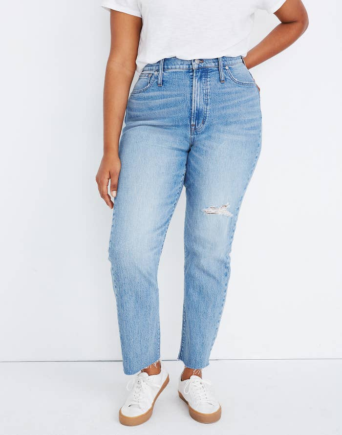model wearing blue tapered leg jeans with a subtle tear on the thigh