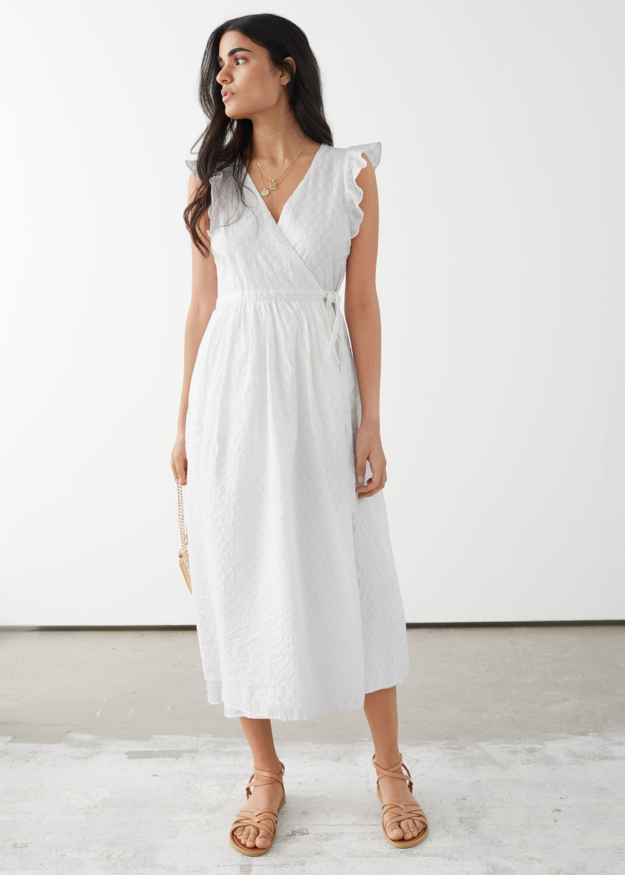 model wearing white wrap midi dress