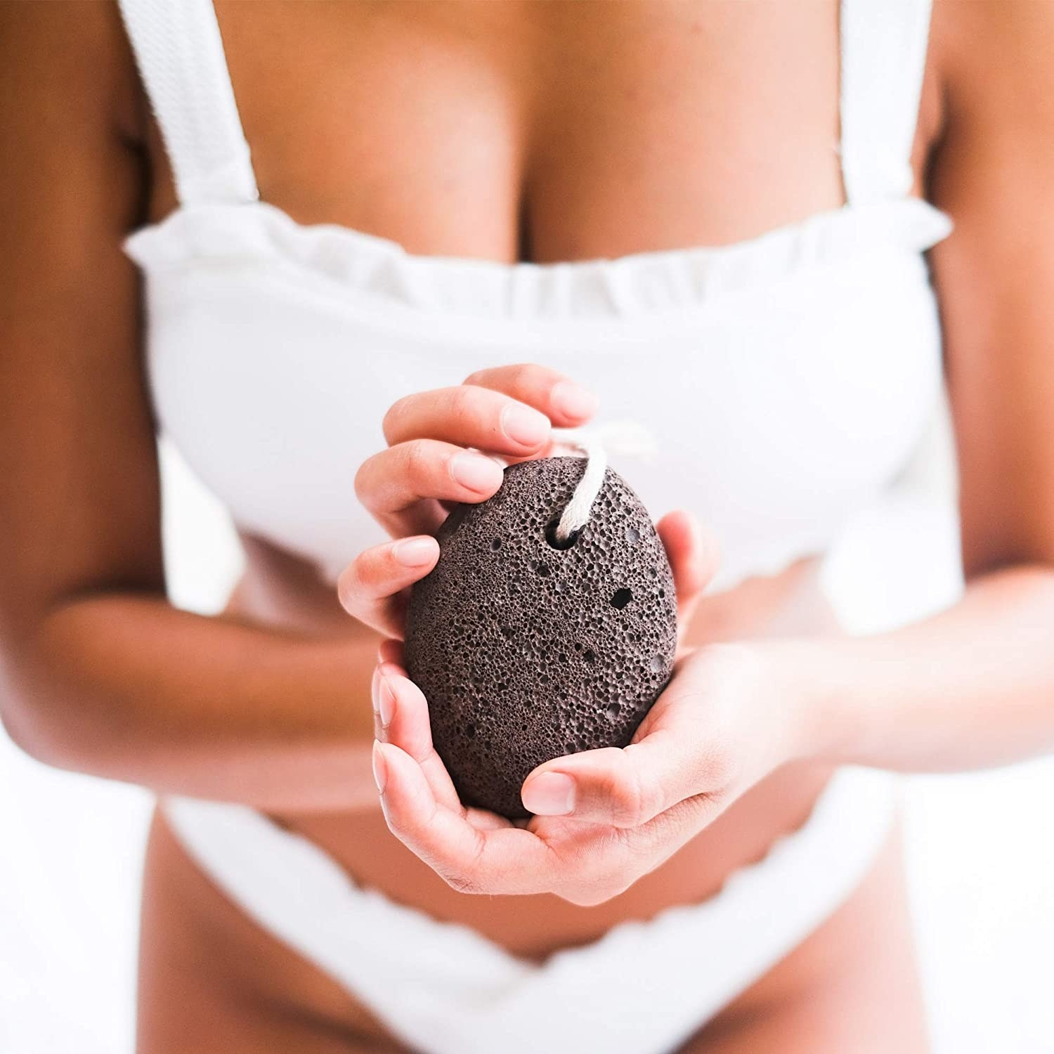 A person holds out a pumice stone towards the camera