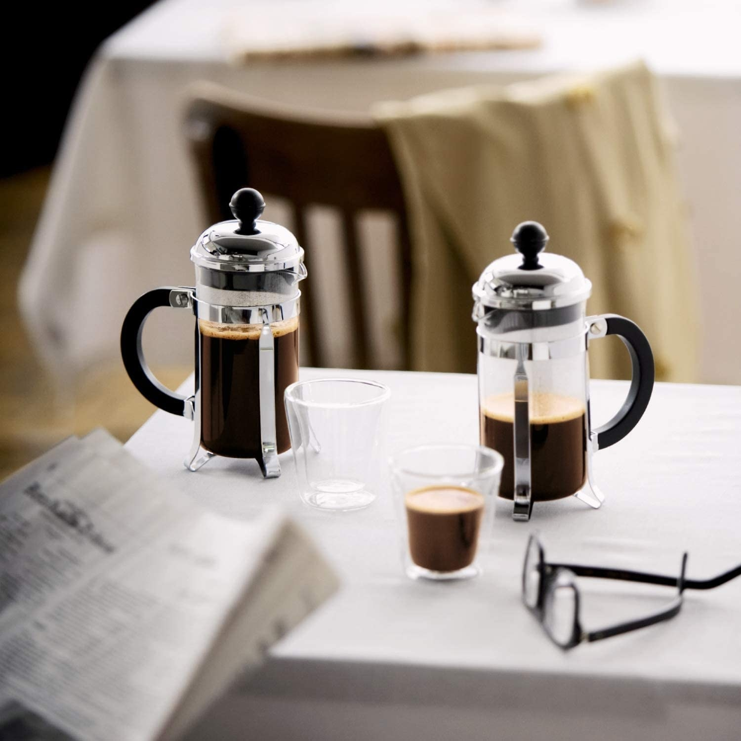 The French press, featuring a glass carafe and chrome top and legs