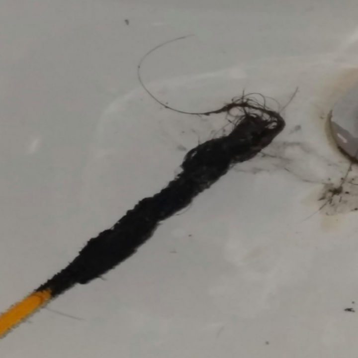 Reviewer shows gross hair and gunk lifted out of drain by yellow FlexiSnake Drain Millipede