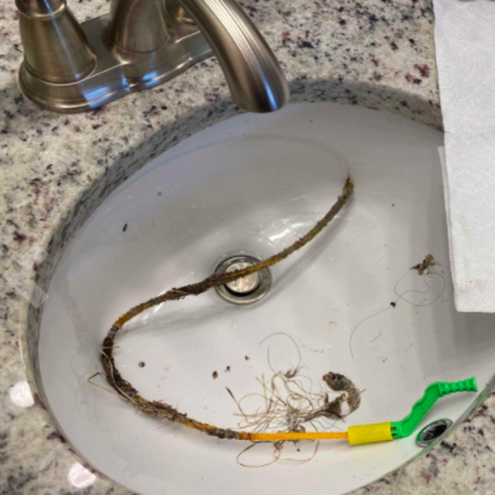 Reviewer shows hair and debris lifted out of bathroom sink by FlexiSnake Drain Millipede