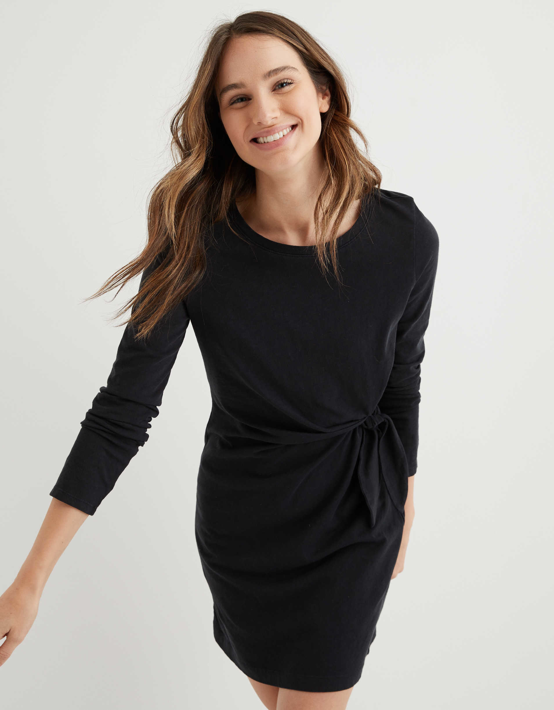 Model wearing the long-sleeved thigh-length scoop neck dress with a tie on the left side in black