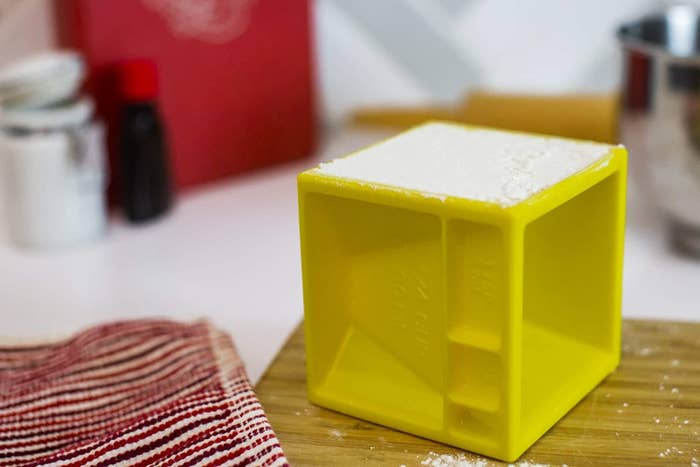 A yellow measuring cube with grooves measuring a