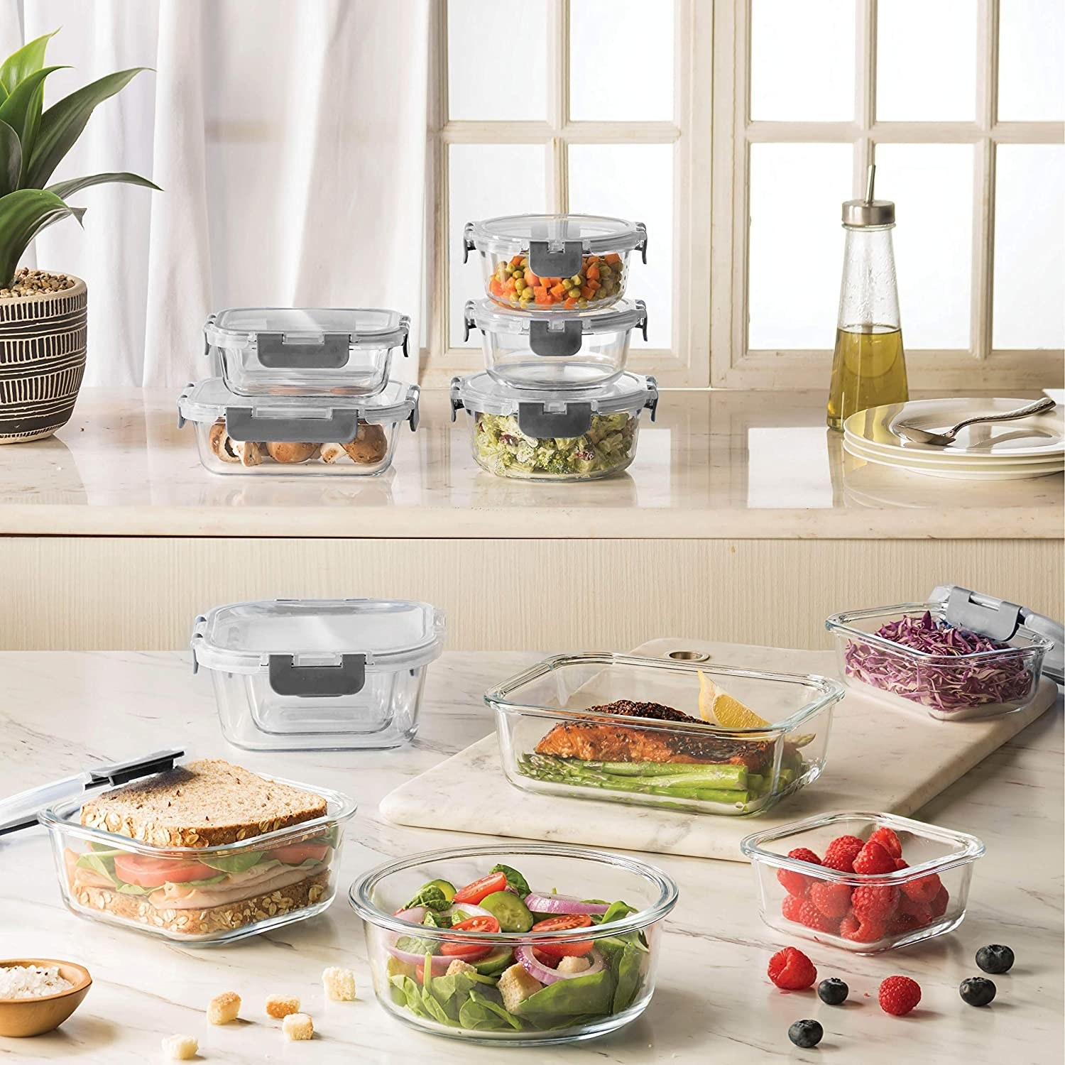 Eleven glass food containers of different sizes on a kitchen counter Each is filled with different food items