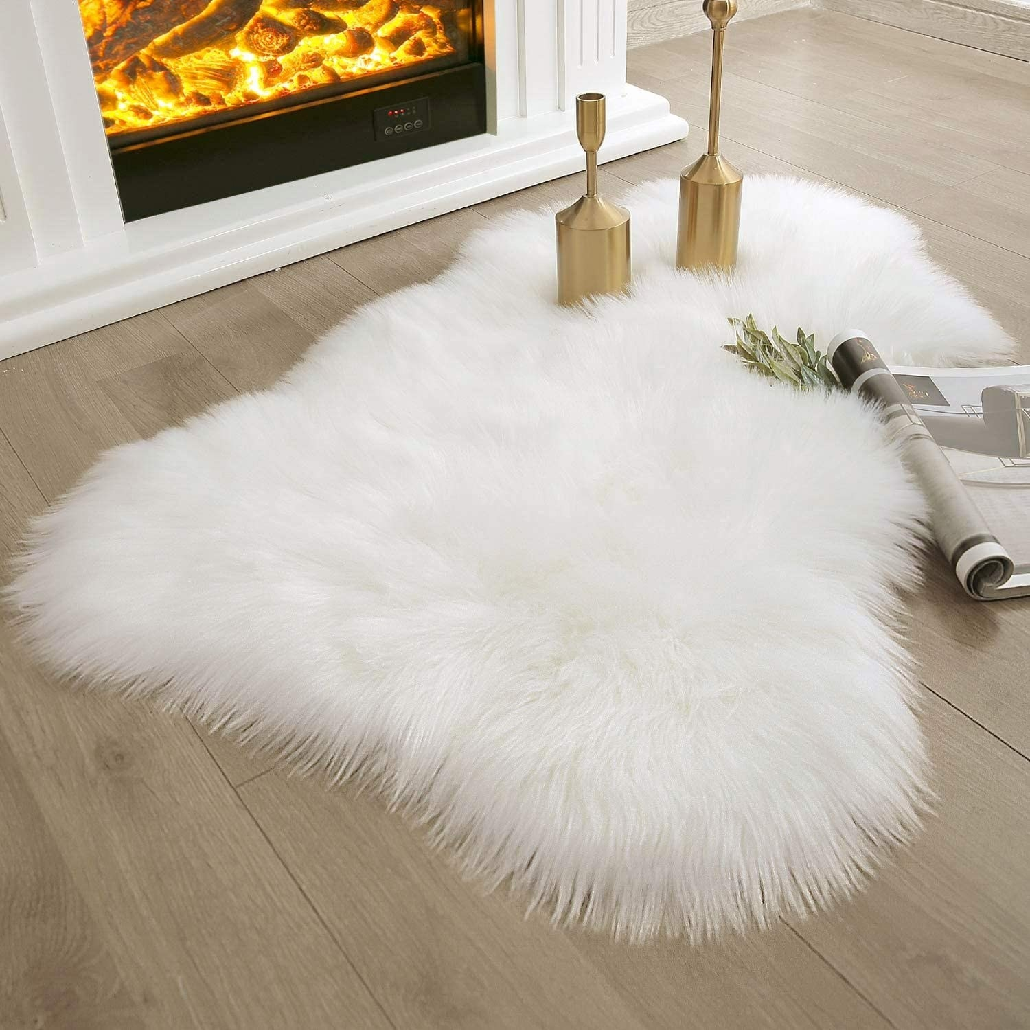 a small, asymmetrical sheepskin-shaped rug with white faux fur in front of a fireplace