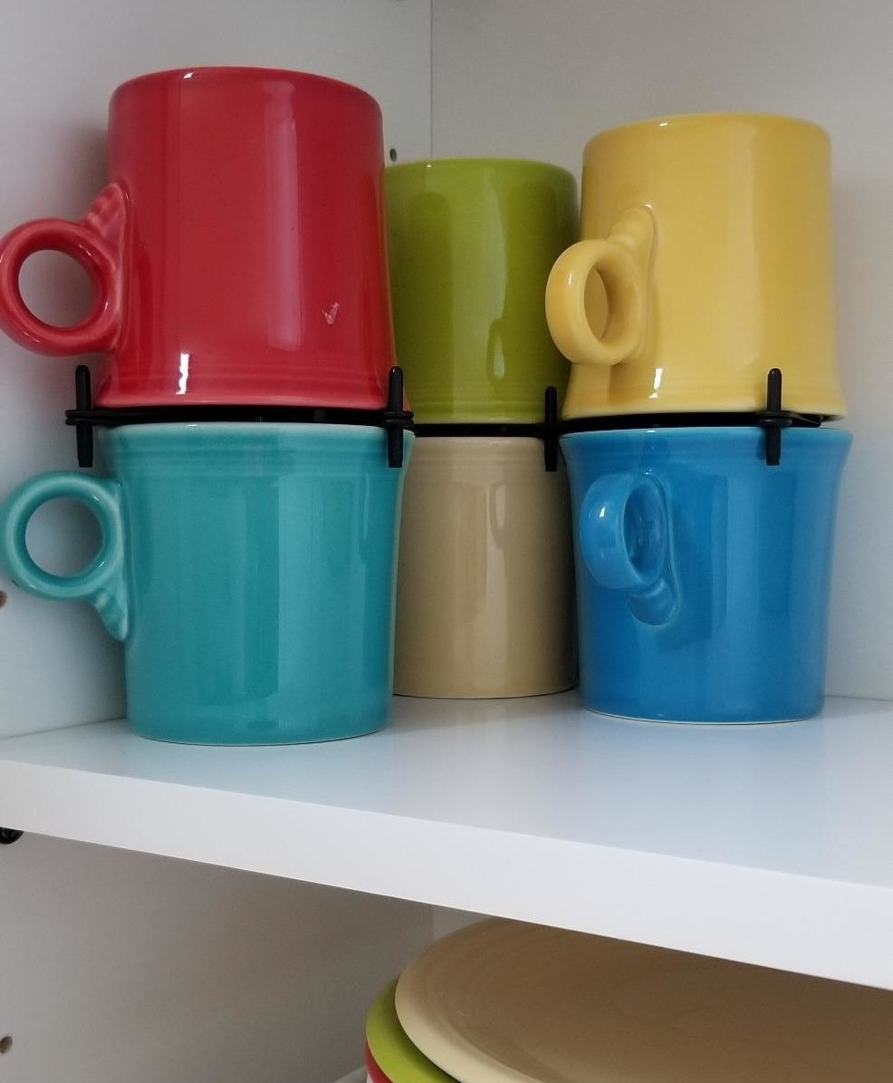 Black organizers allowing colorful mugs to be stacked on top of each other