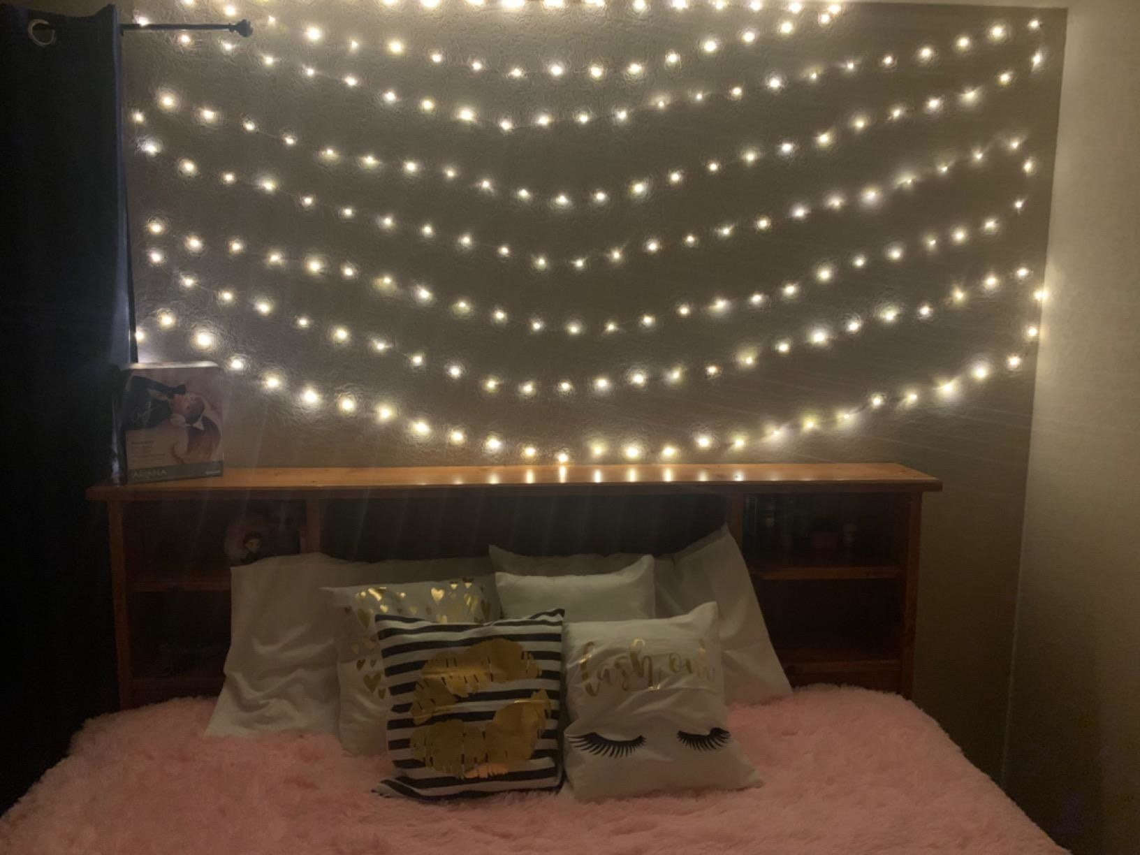 A reviewer showing the string lights hanged in rows above a bed