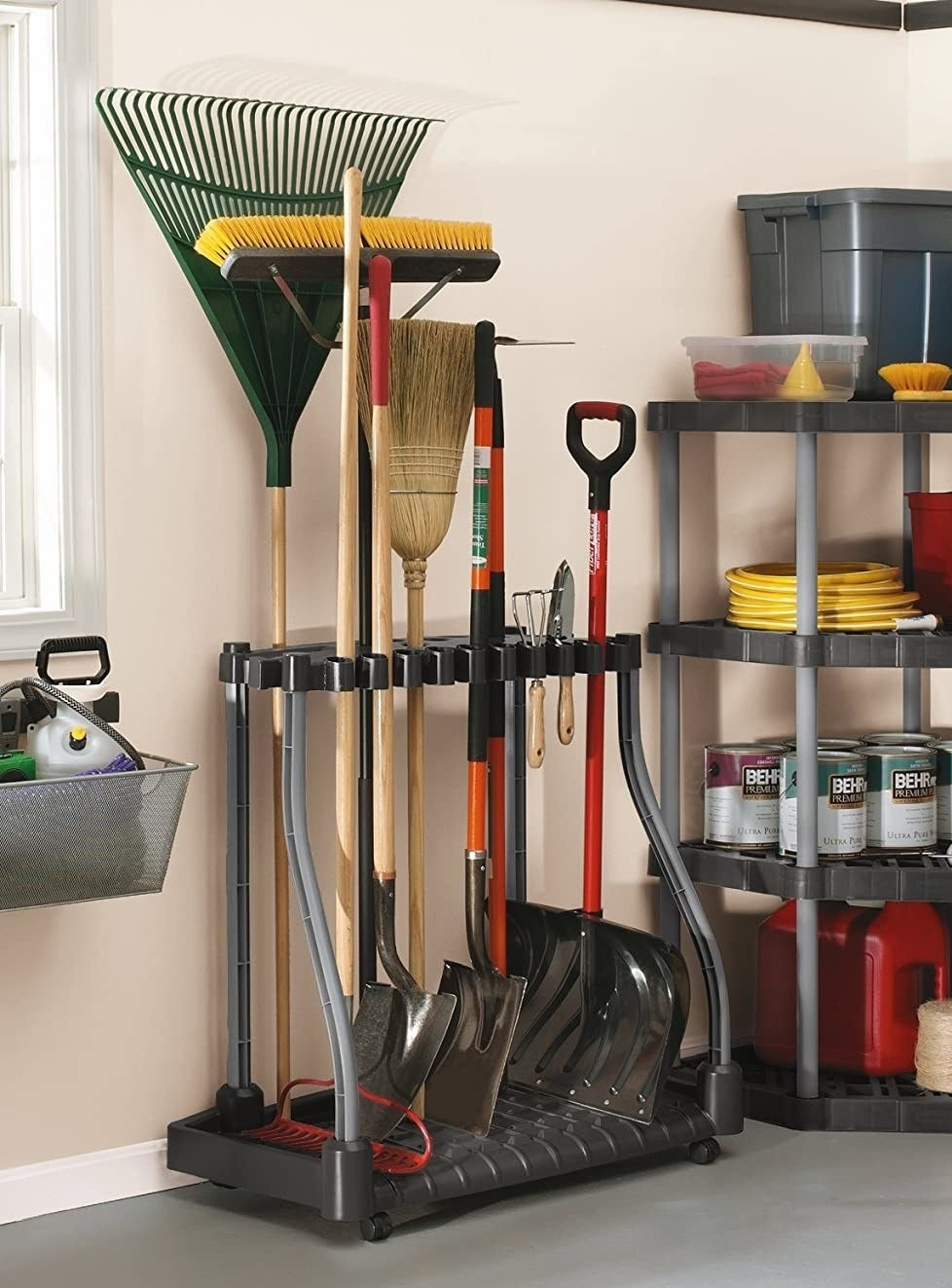 A black and gray plastic tool organizer on caster wheels holding rakes, shovels, and more outdoor tools