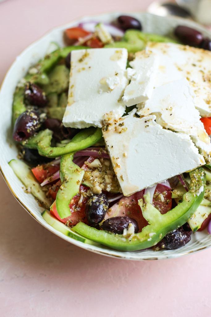 A Greek horiatiki salad with chunks of tomato, cucumber, sliced green pepper, olives, and chunks of feta cheese.