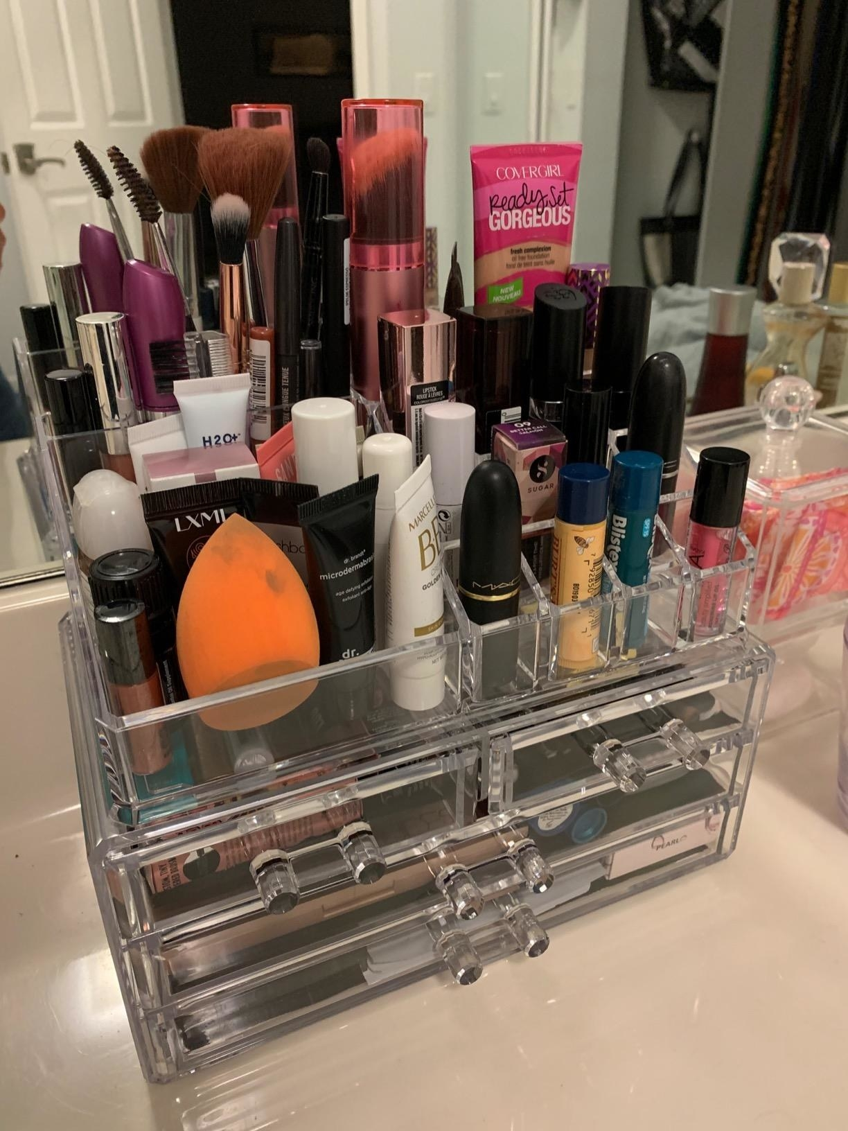 A clear acrylic plastic organizer filled with various make-up products