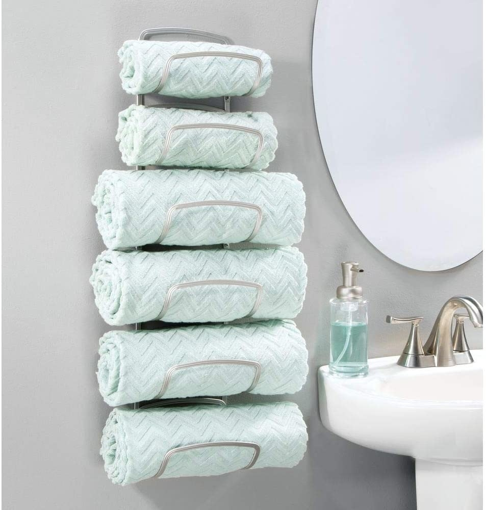 A satin-finish metal towel rack holding four large towels and two hand towels