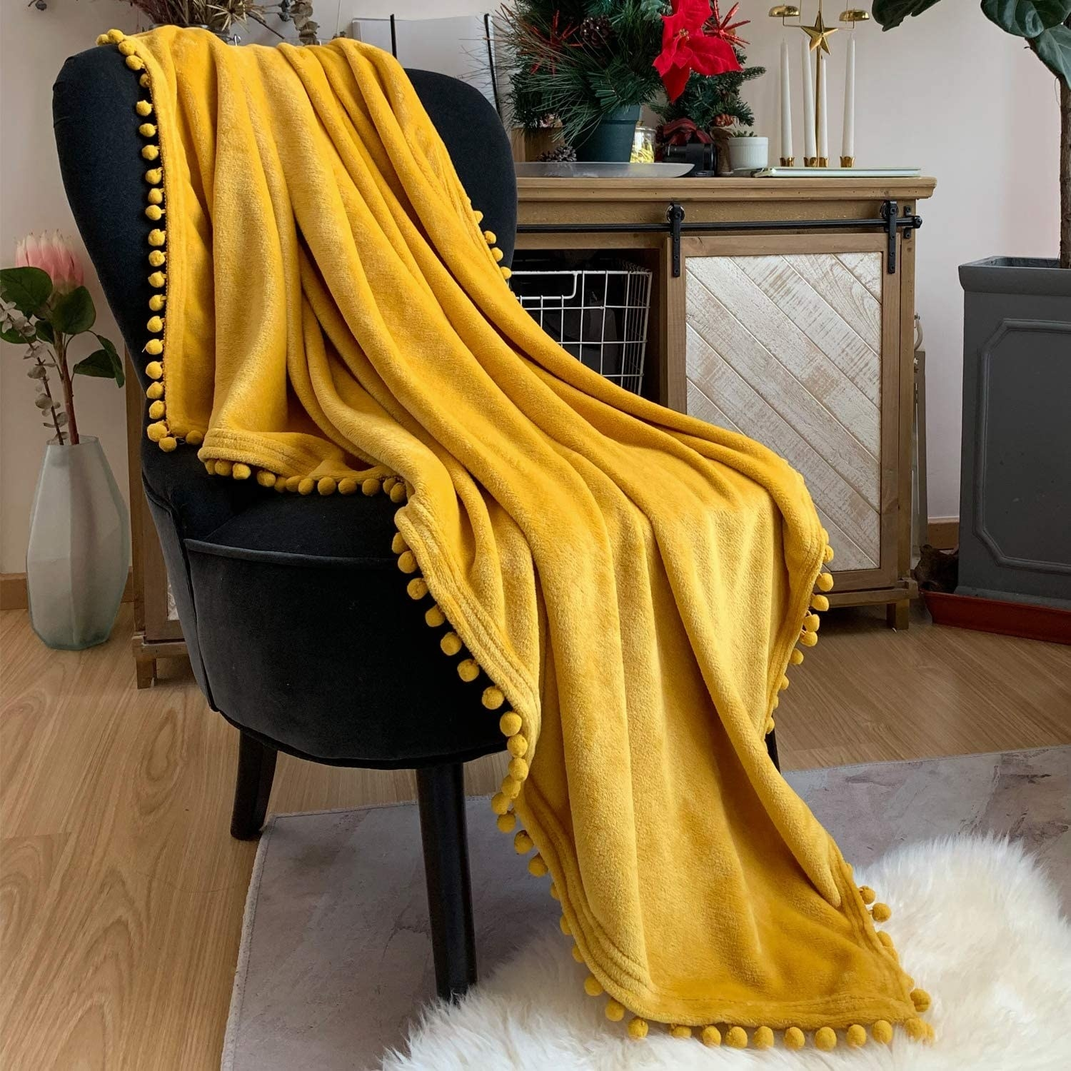 The yellow fleece textured blanket with small pom poms on the edges draped over a chair