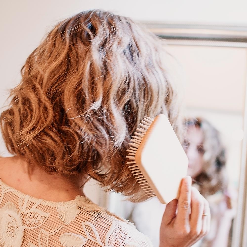 Model brushing their short wavy hair with the brush