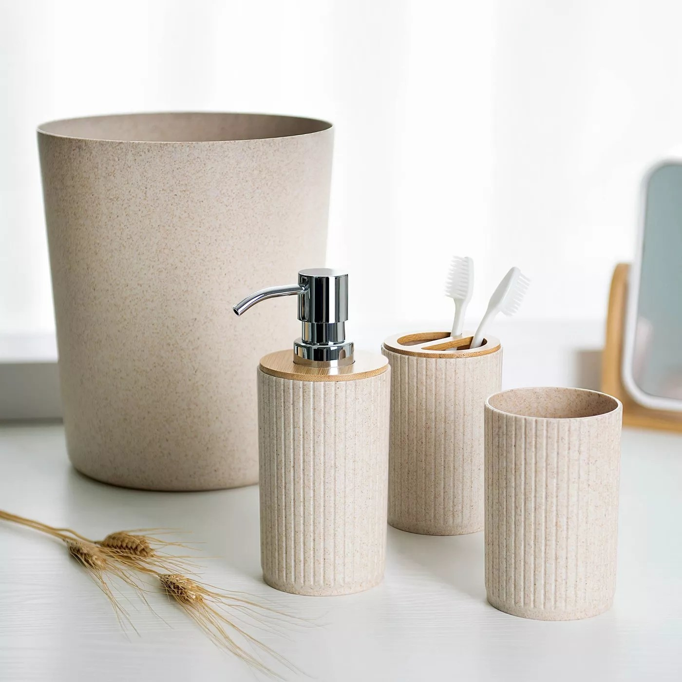 A beige wastebasket, lotion pump, cup, and toothbrush holder