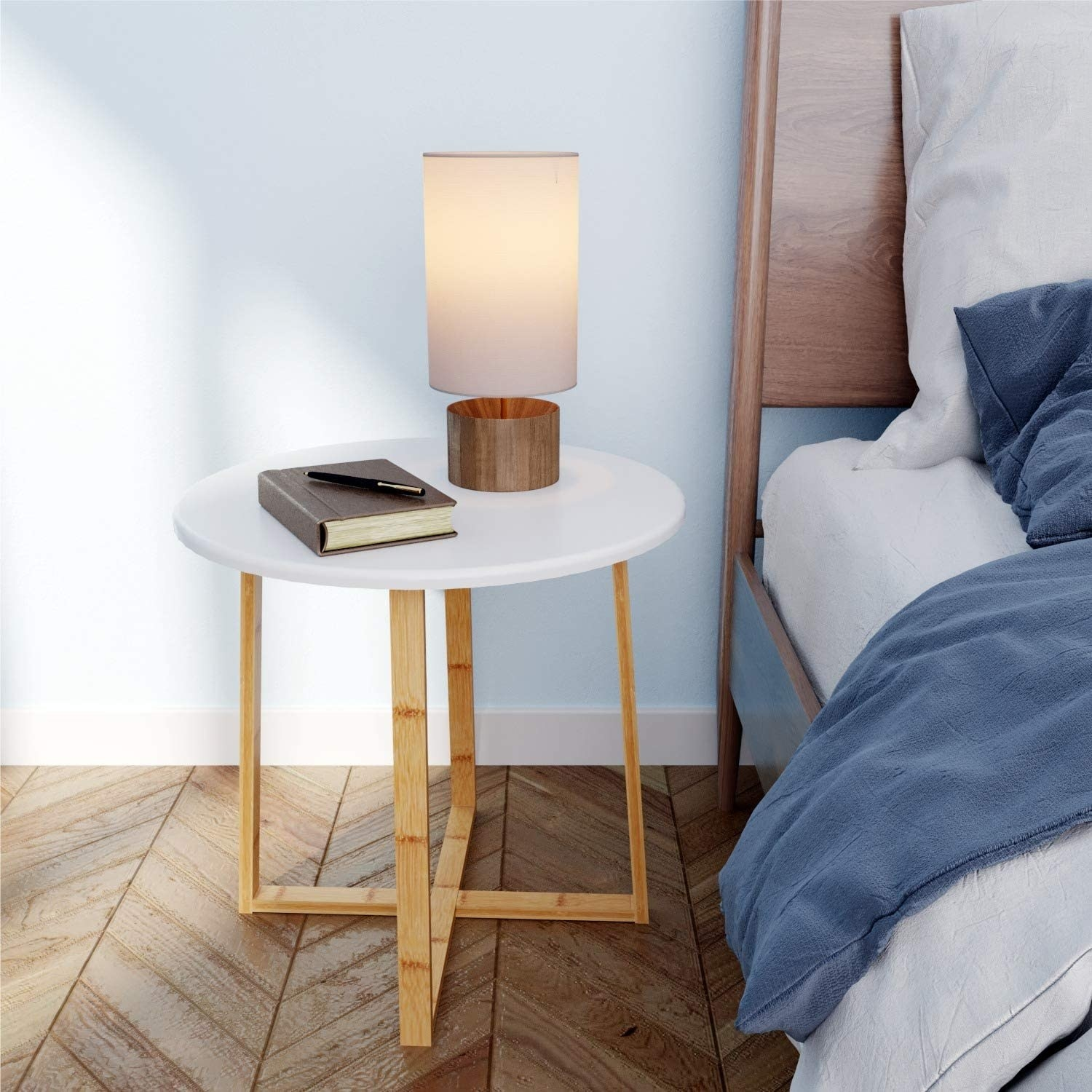 A white circular table with hollow legs