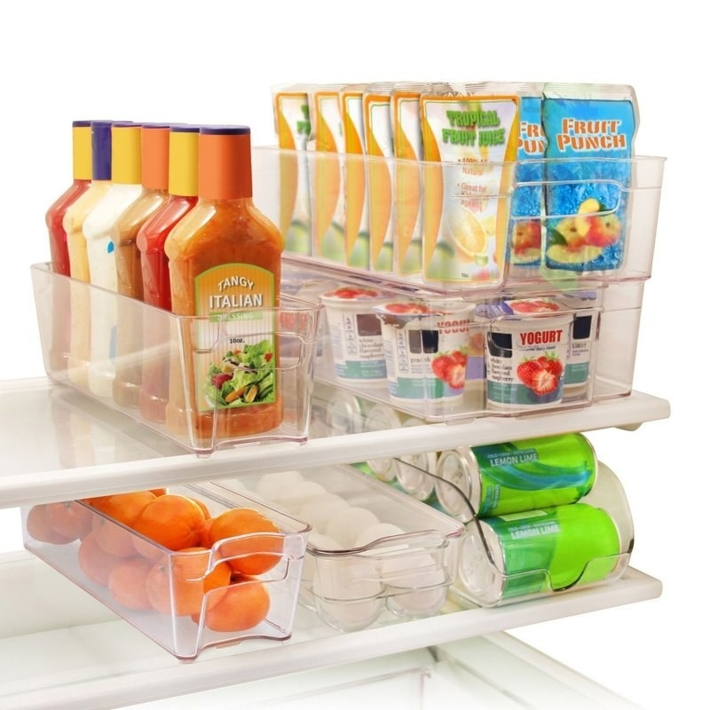 Clear plastic refrigerator bins holding oranges, eggs, sodas, and more
