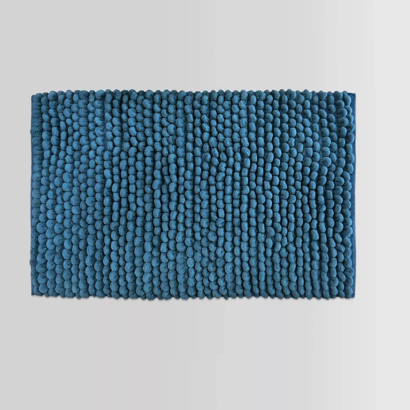 The blue, textured bath rug