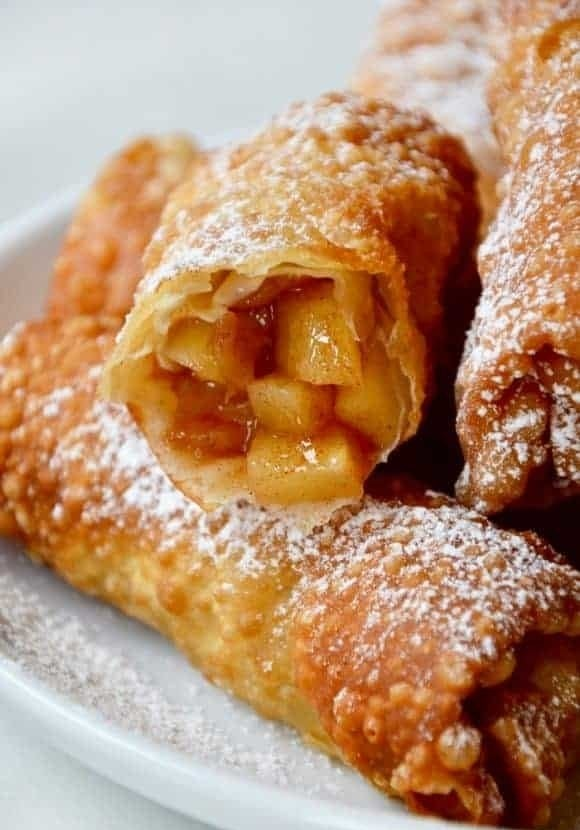 Apple pie egg rolls, one cut upon to reveal a jammy pie filling, topped with powdered sugar.