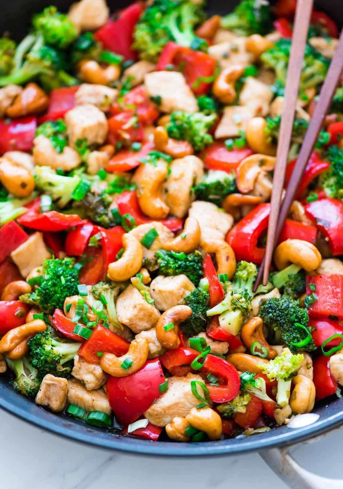 A big bowl of cashew chicken with bell pepper, broccoli, and scallions.