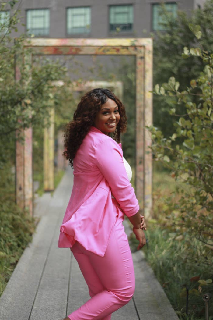 Lyana Blount, owner of Black Rican Vegan wearing a pink suit smiling while she is looking back at the camera in a garden