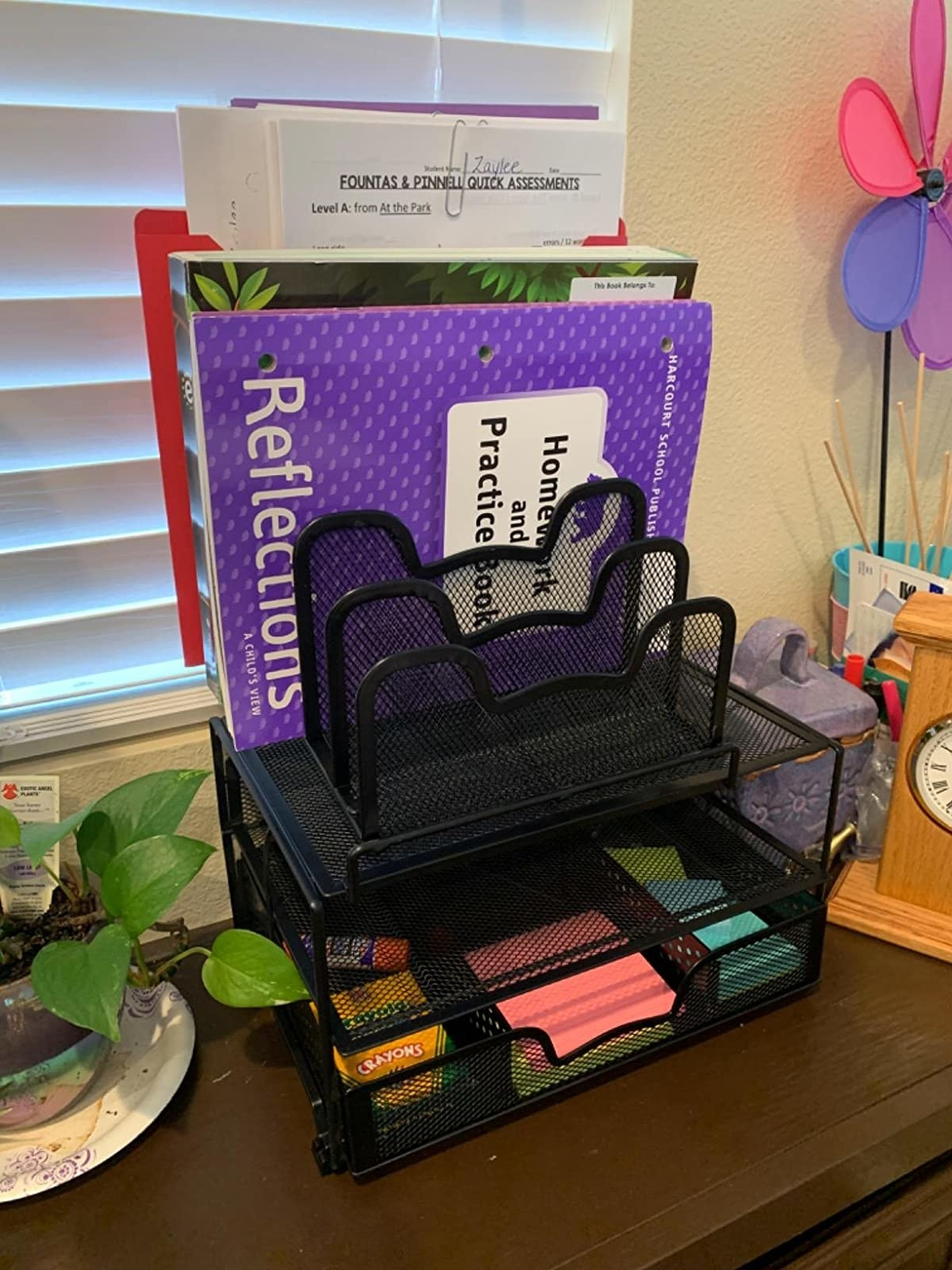 A reviewer's organizer with an assortment of desk supplies inside