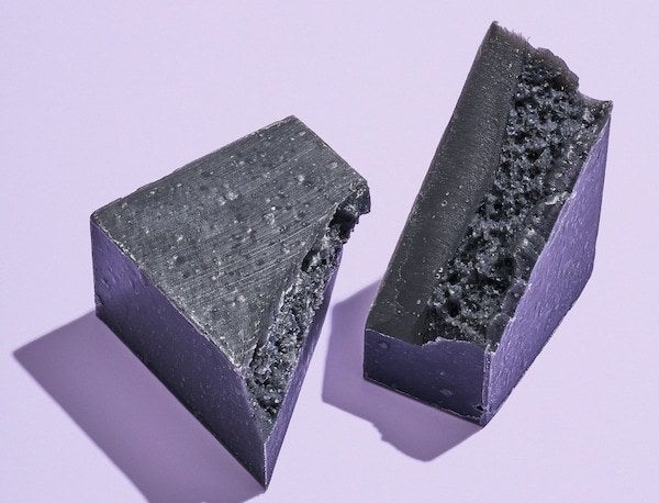 The soap bar cut in half — it's charcoal-colored