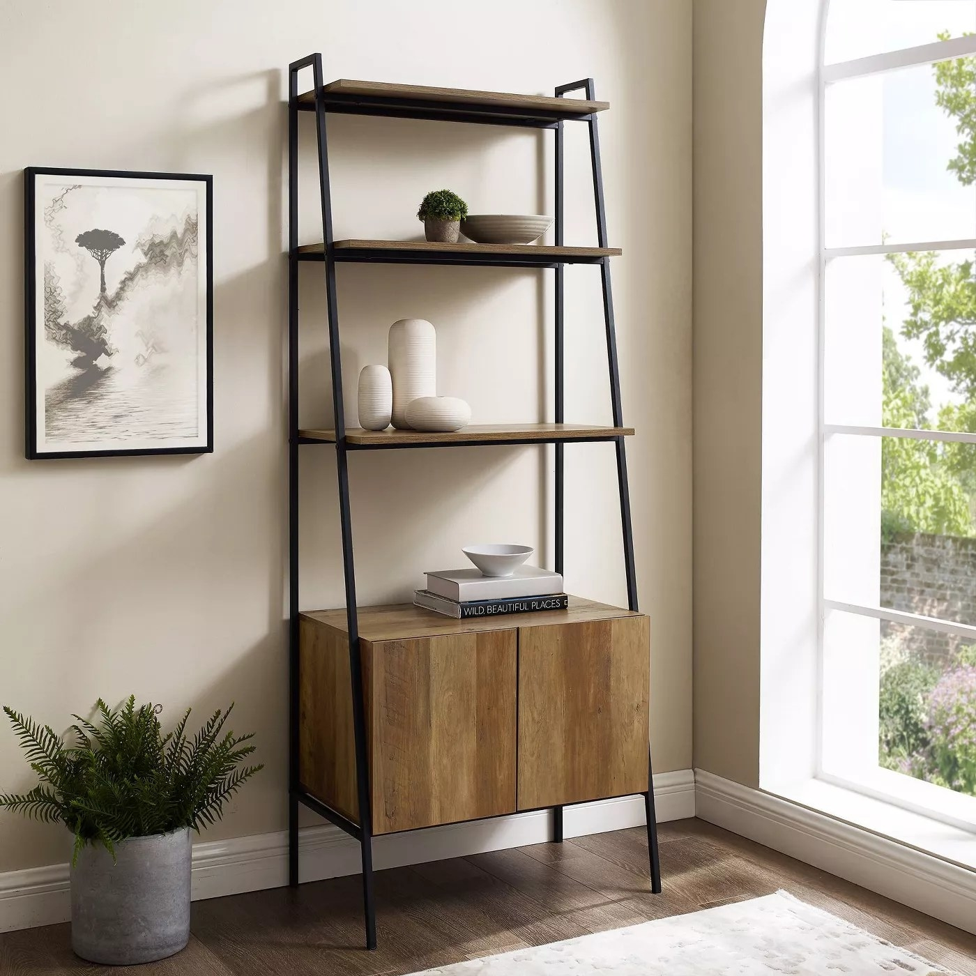 The wooden bookshelf with black railings, three shelves, and a large cabinet