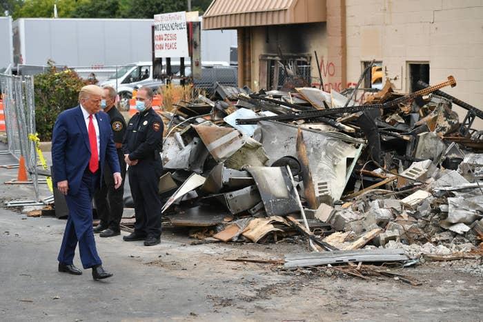Donald Trump walks by debris of a damaged building