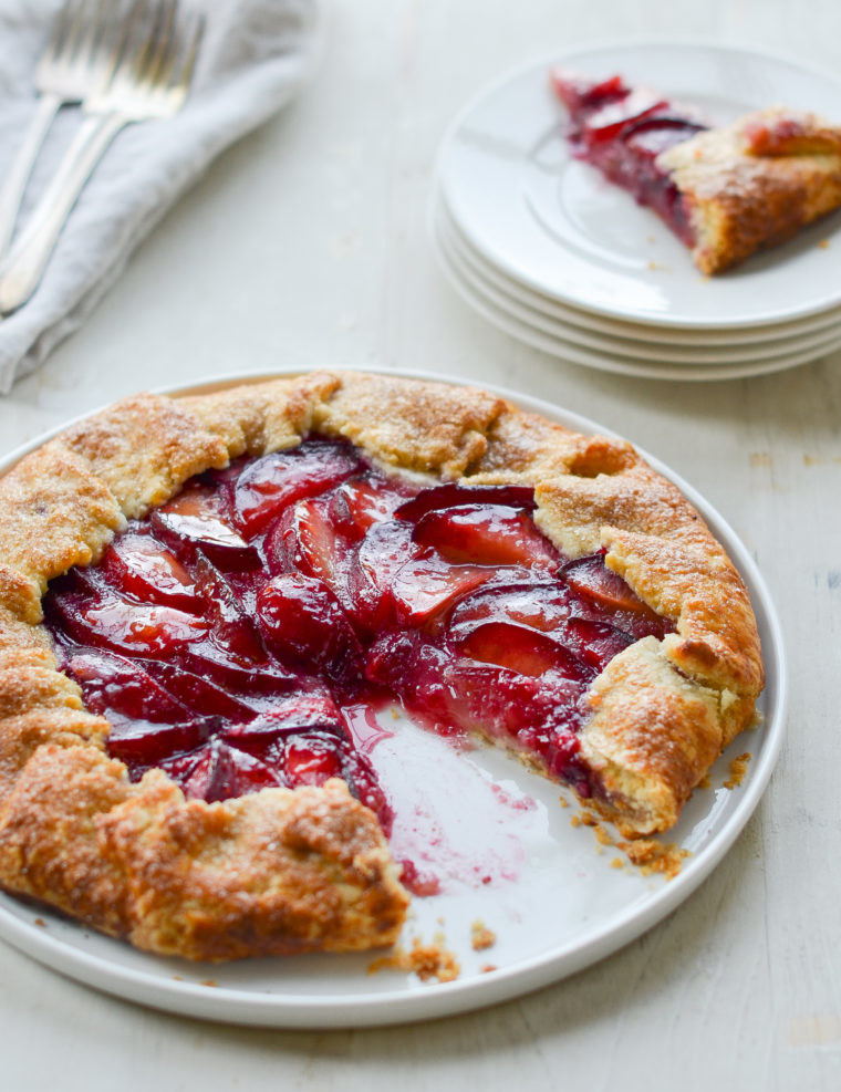 A juicy plum galette with golden crust and a slice missing.