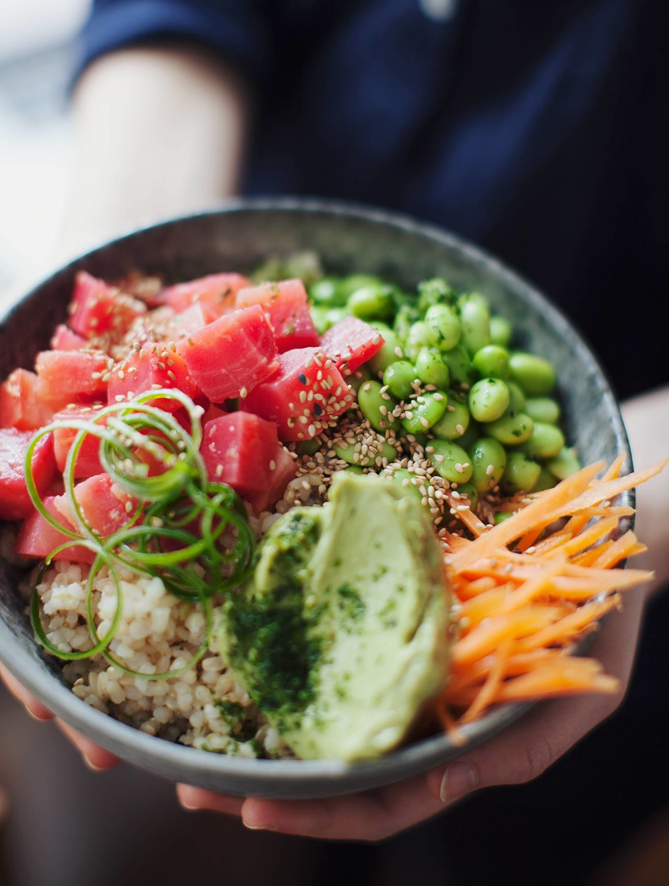 A poke bowl over rice with beets, avocado, carrots, seaweed salad, edamame, and sesame seeds.