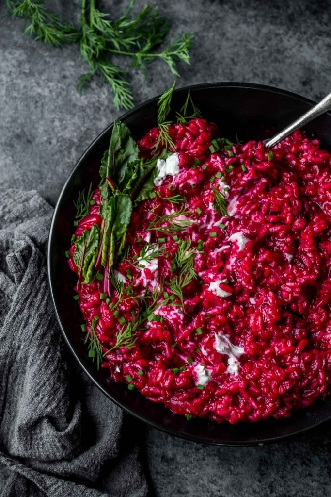 A bowl of vibrant pink beet risotto with melted goat cheese and some fresh herbs.