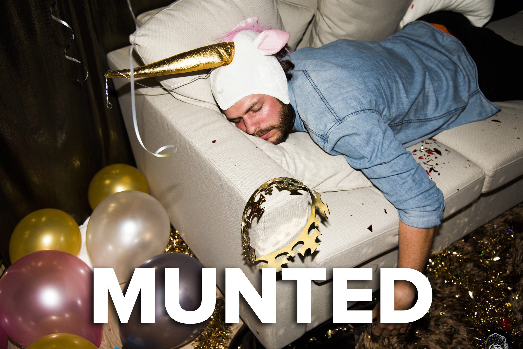 A man passed out on a couch; he is wearing a unicorn horn and there is glitter and balloons scattered around him