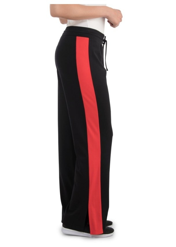 Model wearing black track pants with wide red stripe on side
