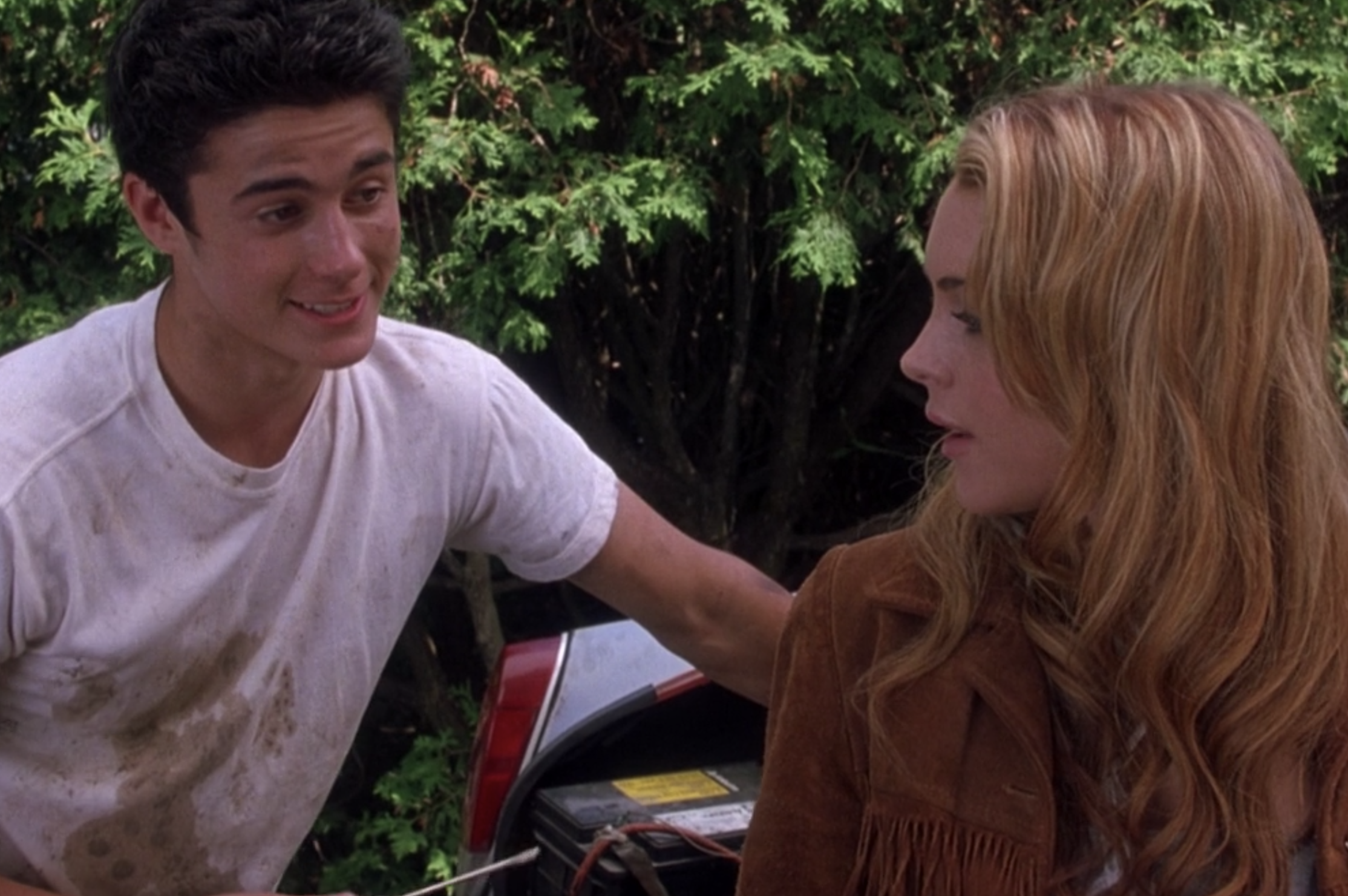 "Eli Marienthal stands next to Lindsay Lohan as Lola and her car in a grease-stained shirt as Sam in ""Confessions of a Teenage Drama Queen"""