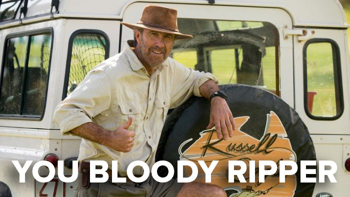 "Russell Coight from ""All Aussie Adventures"" leaning against a car and showing the camera thumbs up"