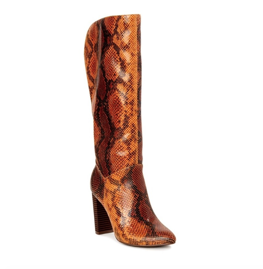 A pair of brown snake skin knee high boots with wooden heel