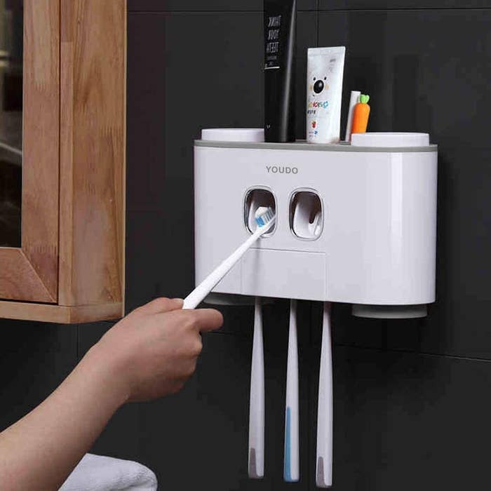 A toothbrush has toothpaste automatically dispensed onto it with three toothbrushes hanging from the caddy