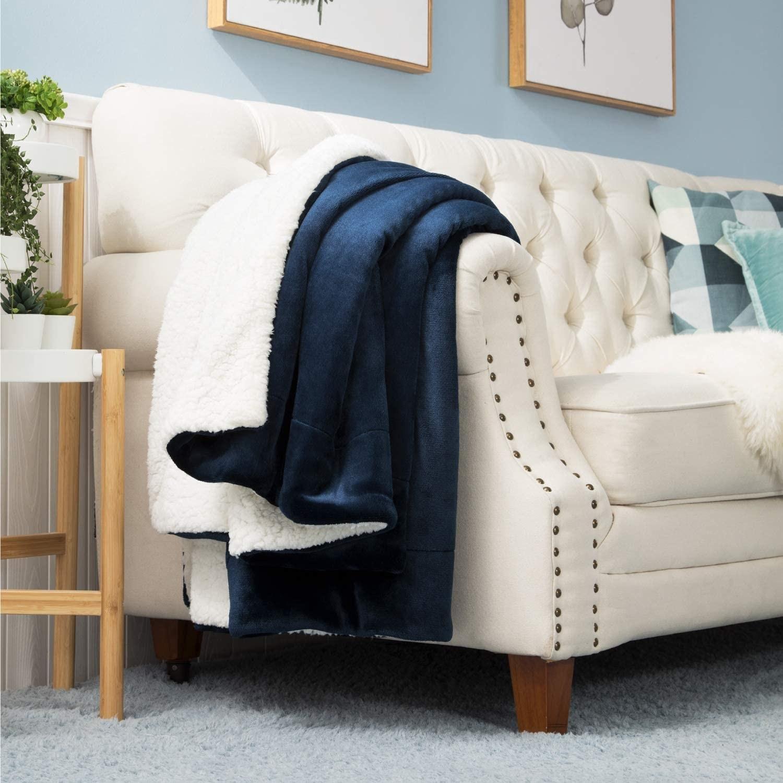 A fleece blanket draped over an arm of a sofa