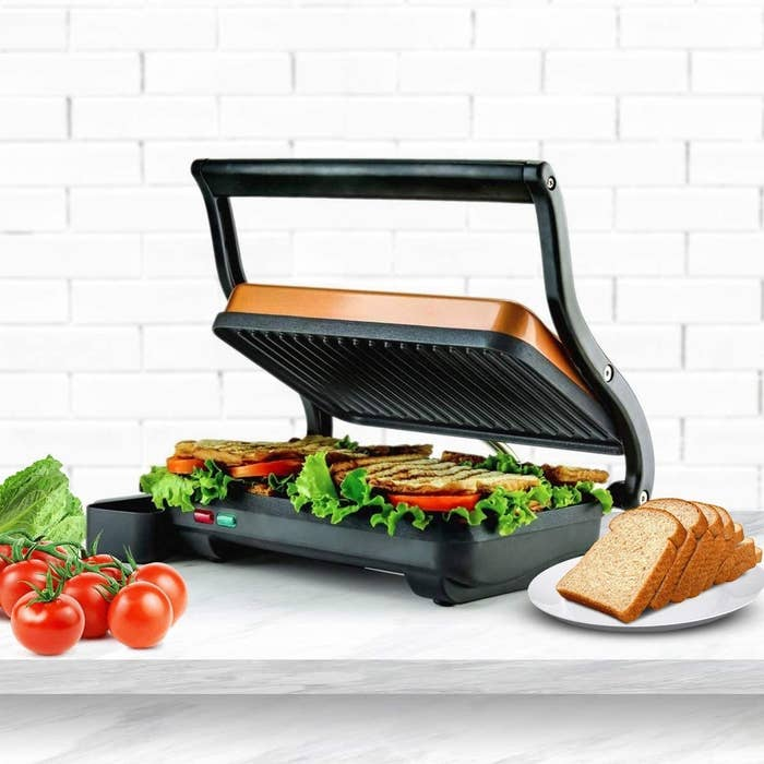 The panini press with a floating lid and a grilled sandwich inside