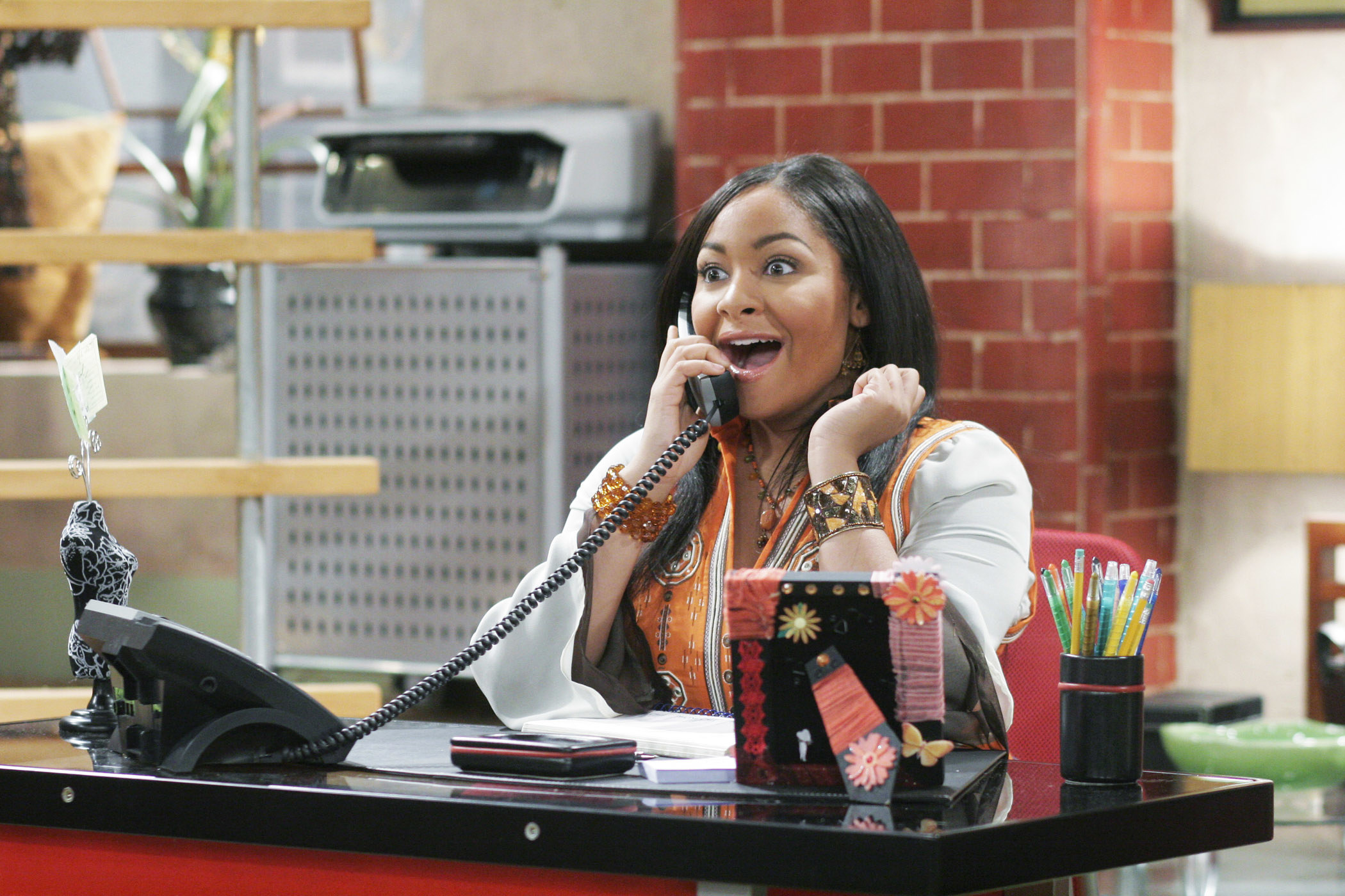 Raven excitedly talks on the phone during a scene on the show