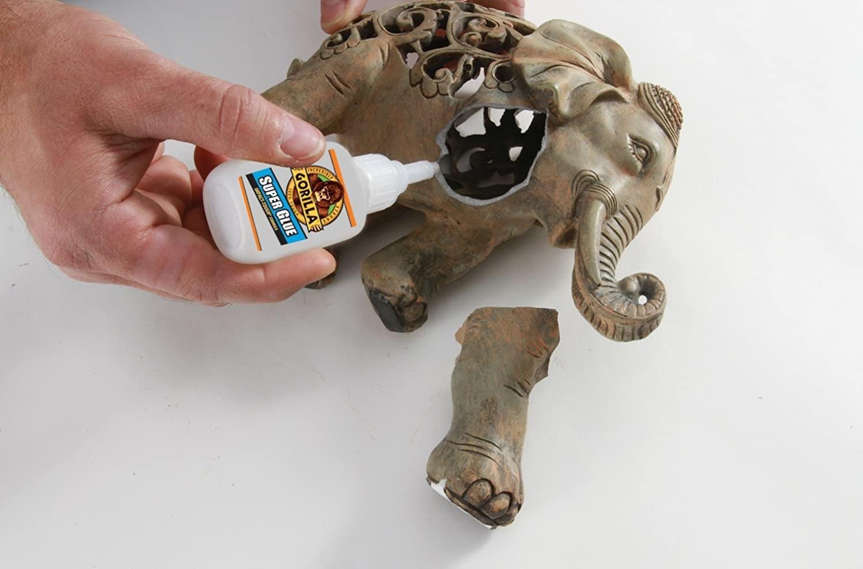 A person gluing a leg back onto a ceramic elephant with super glue