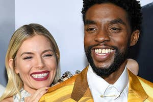 Sienna Miller playfully leaning on Chadwick Boseman's shoulder as he smiles