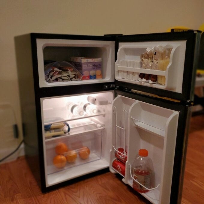 Reviewer's picture of the inside of the mini fridge that shows freezer bin and door shelves