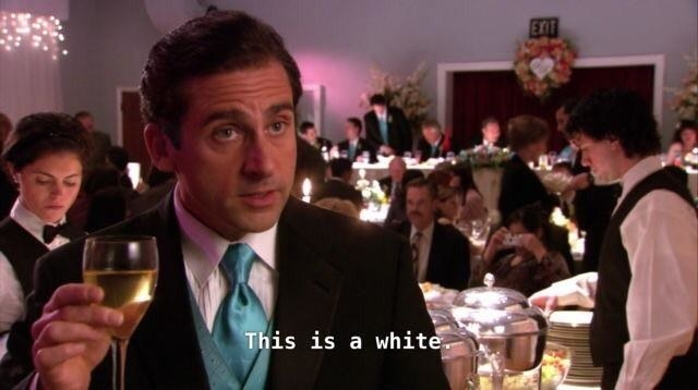 "Michael Scott from ""The Office"" holding a glass of white wine at a fancy event."