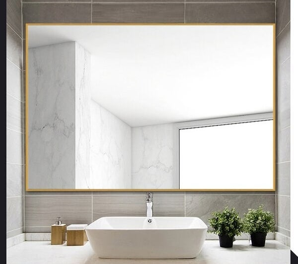 The mirror with gold framing hung horizontally over a bathroom sink