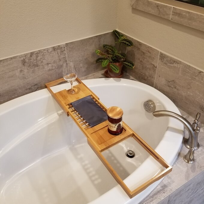 Reviewer's photo of the bamboo tray resting on the tub